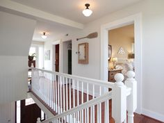 After: An updated staircase railing, a fresh coat of paint and rustic-chic furnishings make the landing sparkle. Walk-out balconies improve ventilation and open up the floor plan.
