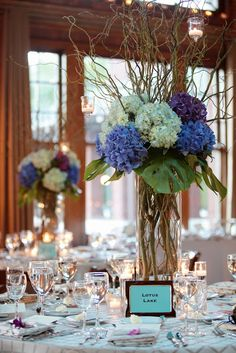 Lovely for spring - centerpieces of different colors of hydrangea, curly willow branches and monstera leaves. The height of this arrangement won't have your guests straining to see each other across the table!