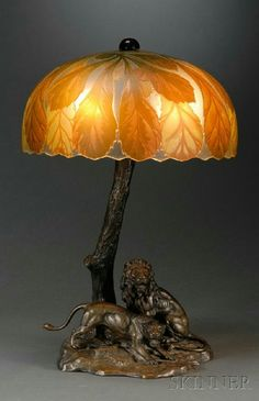 Continental Bronze Lamp Base with Cameo Glass Shade, late 19th/early 20th century, the lamp base with figures of a wary lion and lioness on naturalistic base, the stem formed as a tree trunk, electrified, ht. to top of tree 15 1/4, together with a French cameo glass shade, decorated with horse chestnuts and leaves, with sawtooth edge, dia. 11 7/8 in.