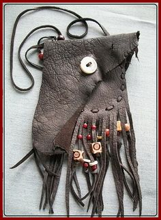Natural ragged edge leather flap and polished deer antler crown button, wood beaded fringes, hand cut lacings, and an extra long neck lanyard