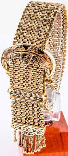 """Lot 1 in the 7.7.15 online & live auction! Exquisite 14kt yellow gold vintage ladies wrist watch. Intricate bracelet style band has a buckle shaped design featuring a """"hidden"""" Lebolt watch under the buckle piece. Bracelet has lovely tassel accents. Buckle piece is accented with black enamel which shows some wear from age and use. Unknown working condition. Measures: 7.25"""" long, marked """"14k Gold"""". An impressive total weight of 45.6 dwt. #Jewelry #Fashion #Gatsby #POGAuctions"""