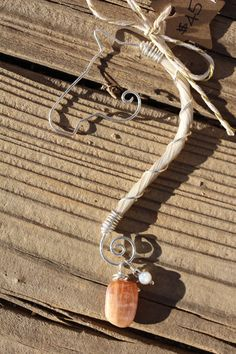 Sterling silver hand crafted wire pendant necklace. This pendant features 2 charms, one is a wrapped Sunstone nugget and the other is a 4mm Mother of Pearl bead stacked with a Bronze Glass Seed bead. .925 20 gauge Sterling Silver wire frame, and 22 gauge wrapping. Pendant is about