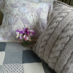 Love the cable knit pillow... love the quilted diamonds pillow... love the knitted blanket... and I love those little purple flowers!