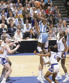 North Carolina guard Michael Jordan drives through the lane amongst a sea of Duke defenders during a 1984 game between the Tar Heels and Blue Devils. Jordan won the Naismith and the Wooden College Player of the Year awards in 1984 before being drafted by the Bulls with the third overall pick. (Heinz Kluetmeier/SI) GALLERY: Duke-UNC Classic Photos | Michael Jordan in College
