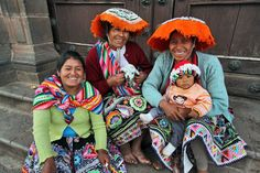 Three Quechua women pose for a photo on the steps of the Qorikancha in Cusco, Peru