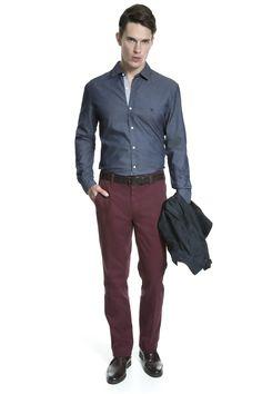 Camisa jeans com micro padrão, calça chino bordô, cinto e bota de couro café e jaqueta marinho em nylon nas mãos.