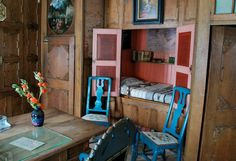 a sleeping cabinet with bold blue chairs; home of artist Carl Larsson