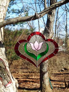 This stained glass panel features a very pretty pink and white streaked tulip accented by bright green leaves which also have streaks of lighter green. The background is created with a clear textured glass. The surround of this piece is made with a bright transparent ruby red