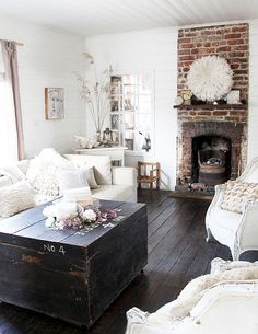 Great contrast created by the dark floors, table, brick fireplace against the white walls and furniture.