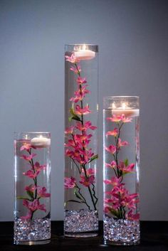 This table decoration will include: 1 – 20 x 4 Cylinder Vase 1 – 14 x 4 Cylinder Vase 1 – 12 x 4 Cylinder Vase Star Flower Silk Floral Strands (not real silk) 3 – Floating Candles 1 – Acrylic crystals bag For more flower water centerpieces you will find Floating Candle Centerpieces, Wedding Table Centerpieces, Centerpiece Ideas, Graduation Centerpiece, Quinceanera Centerpieces, Simple Centerpieces, Centerpiece Flowers, Winter Wedding Decorations, Flower Decorations