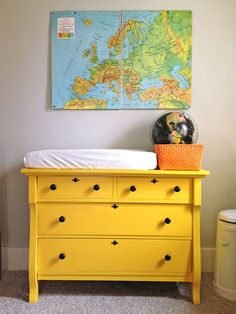 Yellow antique dresser for changing table. Map wall art