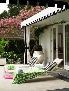 classic... black/white stripe, ivy crawling up over the french door with perfection, punch of green & pink, urns & square planters... gorgeous