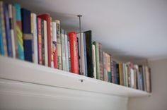 "Ceiling mounted bookshelf. It's basically bookshelf ""trim"". I <3 books."