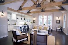Living room in a modern farm house by Meredith Baer with truss-beamed ceiling, dark wood floor, white armchairs with wood arms and a matchin...