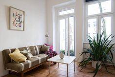 Wohnzimmer einer wunderschön renovierten 1-Zimmerwohnung in Berlin mit gestreifter Couch, bunten Kissen und großen Fenstern.  Wohnung in Berlin.  #Berlin #1roomflat #Wohnzimmer #livingroom
