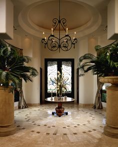 Elegant Entry way and foyer that you enter through beautiful double doors to find a small table under a candle chandelier. The custom tilework defines this space with the design going in a circle around the accent table and chandelier.