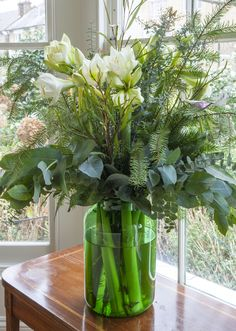 Christmas flower arrangement with fresh seasonal greens and white amaryllis.  Created by Butter Wakefield