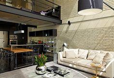 Tons de preto e cinza. Parede com revestimento aparente. Decoração masculina em loft industrial. Apartamento loft. Projeto do arquiteto Diego Revollo.