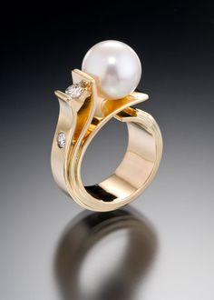 "Fiore Del Mare - An exquisite pearl blooms forth from graceful petals of gold.  The ""Flower of the Sea"" blossoms to reveal a special 10.5 mm (approx.) South Sea Pearl accented by .55 carats total of VS G diamonds in a 14kt yellow gold ring."