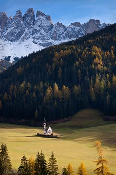 The lone little chapel floats on a sea of green in autumn, Dolomites, Italy