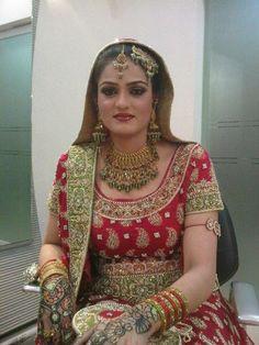 Pakistani/Indian gold bridal jewelry with green stones (zevar): Necklace, tika, jhumar, and long jhumkas