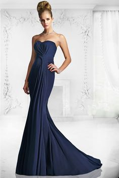 Full length crepe gown with crossover ruche detail. The neckline is an elegant sweetheart shape with pleating over the bust and in to an off centre ruche at the waist. The gown is tailored to the knee and flows in to a full skirt. Product Code: 88106 Colour: Navy
