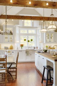 Exposed beams with accent lighting are one of the features in this Sudbury, MA kitchen remodel along with custom painted beaded inset, flat panel cabinets, Caesarstone counters and a large island with a chestnut countertop.