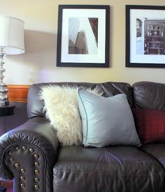 feather filled pillows, brown leather couch, black & white photos