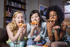 Three women eating pizza on couch - Betsie Van Der Meer/Getty Images