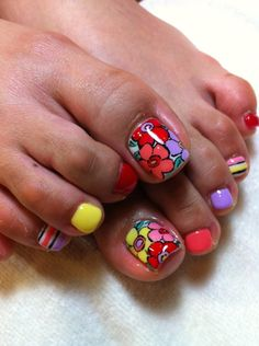Bright floral and striped toenail art with solid accent nails in  complimentary colors, free hand pedicure nail art