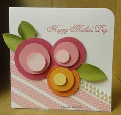 Whimsical flowers created from circle punches take center place on this handmade mother's day card. Washi tape or paper scraps on a diagonal slant allow great white space for the sentiment. Pearls dress it all up for mom!