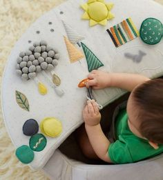 A young baby explores different textures in an activity chair that he received as a first birthday gift.