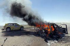 El piloto chileno Javier Campillay pasa junto a un auto mientras se incendia.