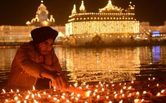 #Diwali: the festival of lights - An Indian Sikh devotee lights oil lamps at the Golden Temple in #Amritsar.