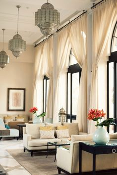 Moroccan inspired room with long white curtains and Moroccan chandeliers. Via A Casa da Va.