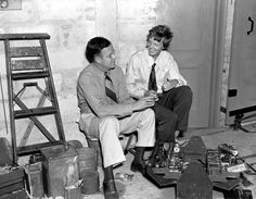 American aviatrix Amelia Earhart, right, and her husband, publisher George Putnam, talk over plans for Earhart's second attempt to fly around the world. They are in a hangar where Earhart's plane Electra is being prepared for flight in Miami, Fla., May 29, 1937