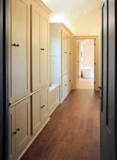 Hallway lined with custom-built in closets that leads to master bathroom.