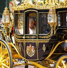 Queen Elizabeth II being driven down The Mall in a horse drawn carriage to attend the State Opening of Parliament on May 27, 2015 in London, England.
