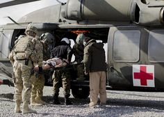 Flight medics from Task Force Knighthawk, 2nd Battalion, 3rd Aviation Regiment, and the Kandahar Air Wing, lift a simulated casualty into a UH-60 Black Hawk helicopter during the culminating exercise of a four-week tactical combat casualty care and basic life support training course, Jan. 4, at Kandahar Airfield, Afghanistan. The course certified graduates as trainers in casualty care and life support, allowing them to train and certify other medics at the Kandahar Air Wing.  (Sgt. Luke Rollins)