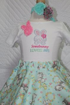 """This little outfit has a beautiful full twirl skirt that has Vintage Easter bunnies on it.  It is a pale mint green color.  The shirt has an adorable little Easter bunny and the words are embroidered """"Somebunny loves me"""".  It also has a cute pink rosette Easter bunny on the shoulder of the shirt.  The outfit also comes with a very pretty headband made with all the colors of the outfit.  I can personalize the shirt for you, just put your child's name in the notes section of your order.  I do…"""