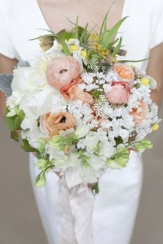 wedding bouquet of soft greens, peach, white and pops of marigold