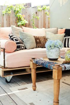Pallet sofa with plumbing pipe arms and beautiful pillows.