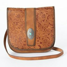 Western leather crossbody bag. Coming soon New.This Western-chic bag boasts a floral-tooled finish and turquoise-embellished silvertone hardware. An adjustable crossbody strap adds hands-free convenience.  5.75'' W x 6'' H  21'' shoulder drop  Leather / zinc Bags Crossbody Bags