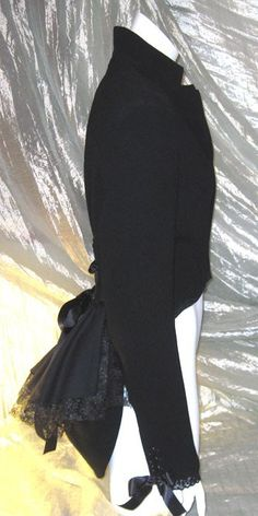 Black Victorian style corset jacket / bustle coat with padded shoulders (fully lined). Adjustable cinch-up corset detail in back with wide double-sided satin ribbons. Jacket waist cut-away in front, longer in back, with multi layered bustle in back. Reconstructed & upcycled from a lightweight ladies suit jacket, brand new with tags attached. Professionally finished and built to last    Size : 14/16 UK (13/14 USA) (40/42 EUR)    Bust : 39 - 41 inches    Waist : 33 - 35 inches    Length from…
