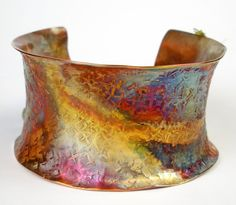 """Hammered Copper Cuff Bracelet, Anticlastic Forged Copper Cuff- Colorful Copper, Womens Copper Bracelet, Heat Patina-Tempest    """"Tempest """"    The design and metal work: I began with a piece of copper sheet metal. The copper was repeatedly annealed (heated with a torch) during the design process, texture hammered, and hammered into an anticlastic oval. Once the design was complete, I then tumbled the cuff for added strength and shine. As one of the finishing touches, I selectively applied a…"""