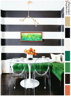black and white dining room with emerald green accents, black and white striped walls, white tulip table, clear acrylic ghost chairs, dark brown wood flooring, emerald green upholstered bench, bright green wall art, modern brass light fixture, bone white monogrammed pillow, blood orange accents, pantone lush meadow