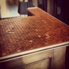 A countertop adorned with pennies! Hint: Only the pennies around the edge or glued in place! The rest just stay in place. So neat! #penny #creative