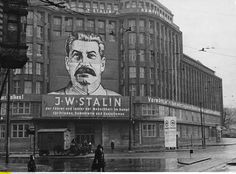 """Berlin, district Prenzlauer Berg, location of the central committee of the SED (Socialist Unity Party of Germany). Torstrasse 1 / Prenzlauer Allee 249 (former dep. store Jonas; built 1928/29). Exterior view with large poster """"J.W.Stalin: leader and teacher of humanity (…) """". Photo, undated (c. 1950s)."""