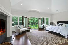 Romantic and beautiful is this simply designed master suite with a full working fireplace sitting area and wide open doors to the woods in the Hamptons how divine by Perello Building Corporation, Southampton, NY.