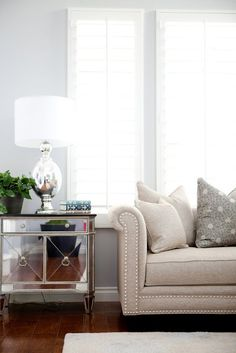 LOVE this theme. Pale gray/blue walls, beige couch with nailheads accents, mirror furniture, WHITES...